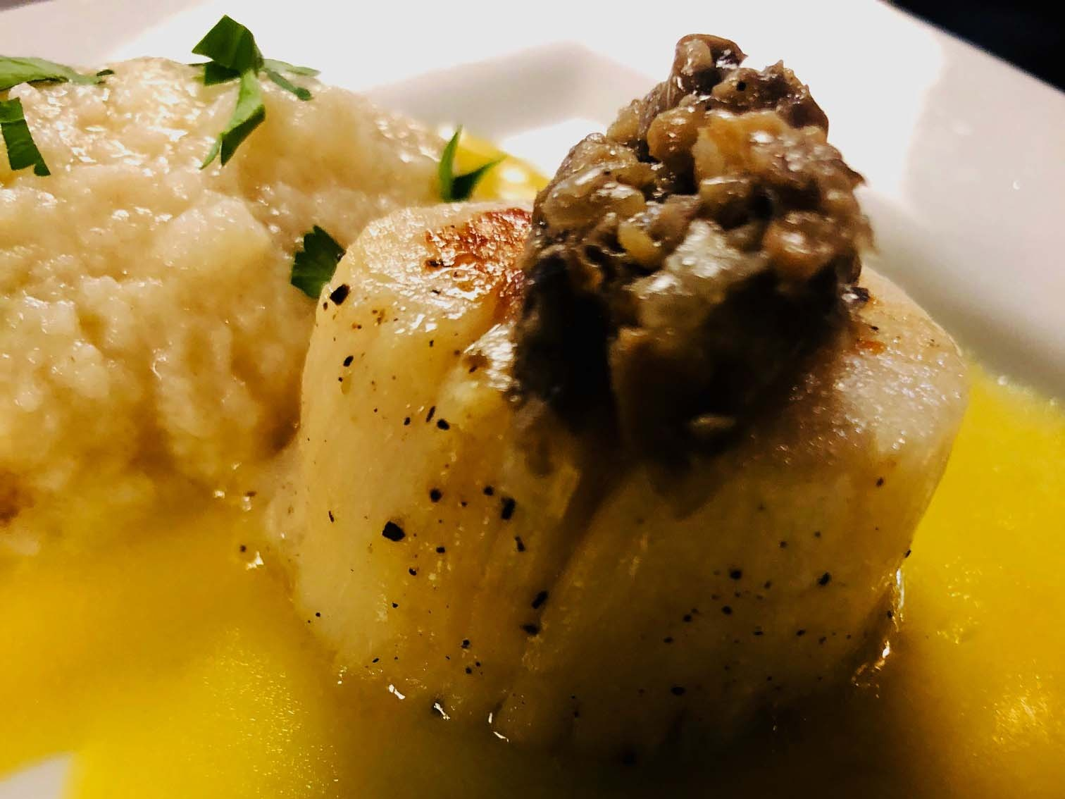 Pan seared scallop with a duxelle of mushroom, pike quenelle and a saffron beurre blanc