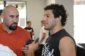 Eddie Constantine (left) at a media day circa 2009, interviewing Strikeforce world lightweight champion Gilbert Melendez (right).