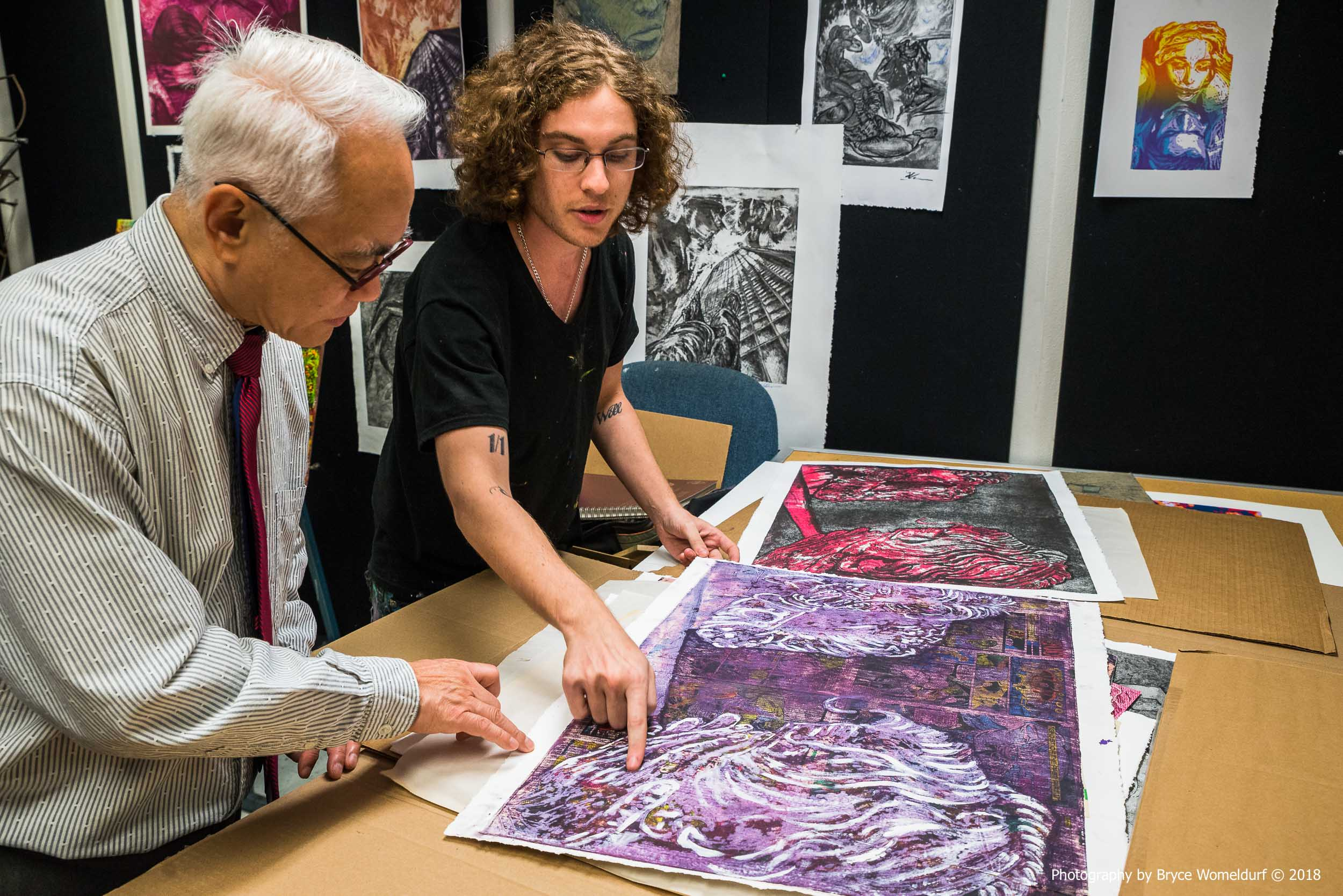 Artist Logan Bryce Holeve showing Dean James Moy his print work