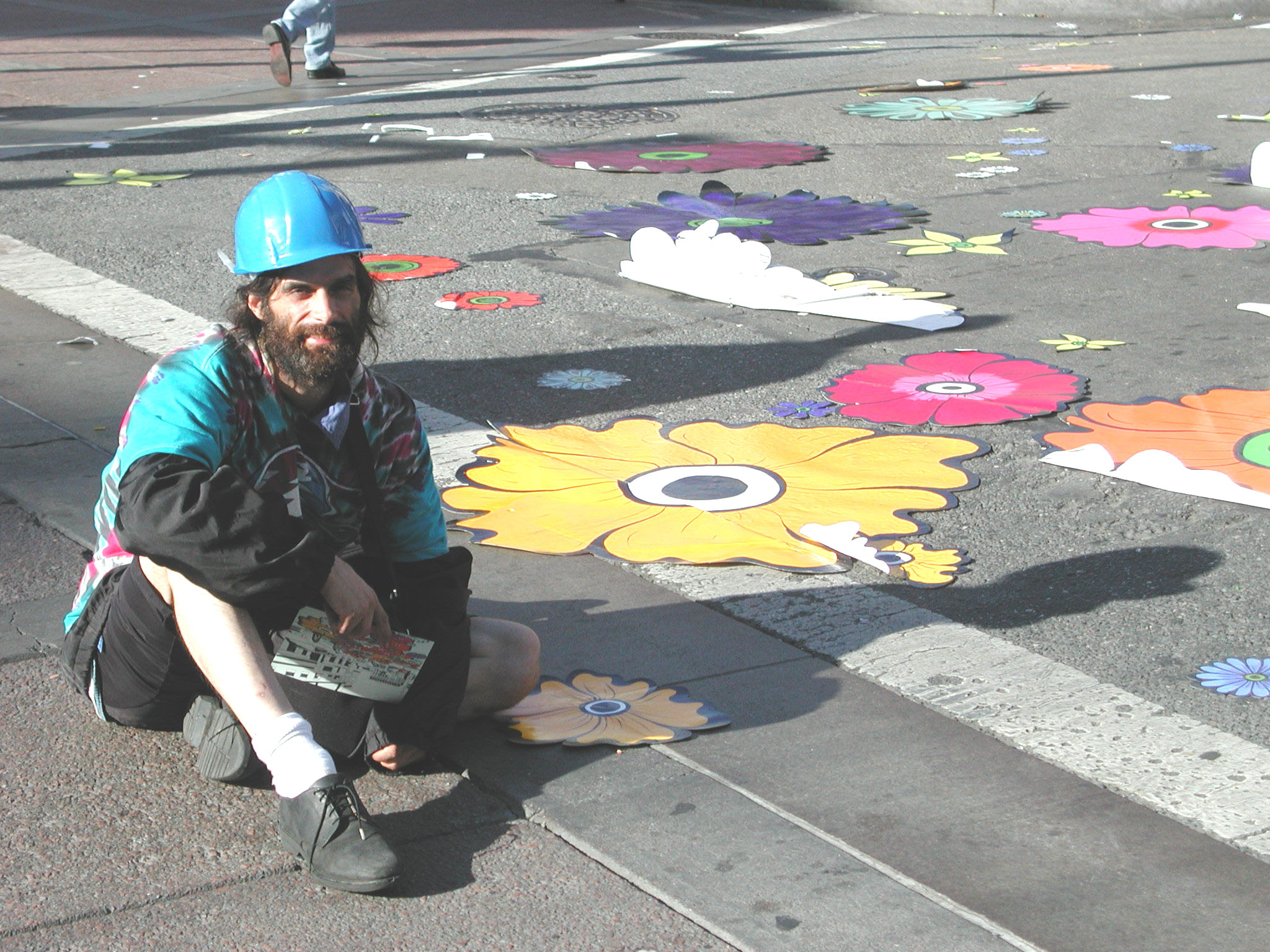 man in hard hat on ground with flowers holding card 2.jpg