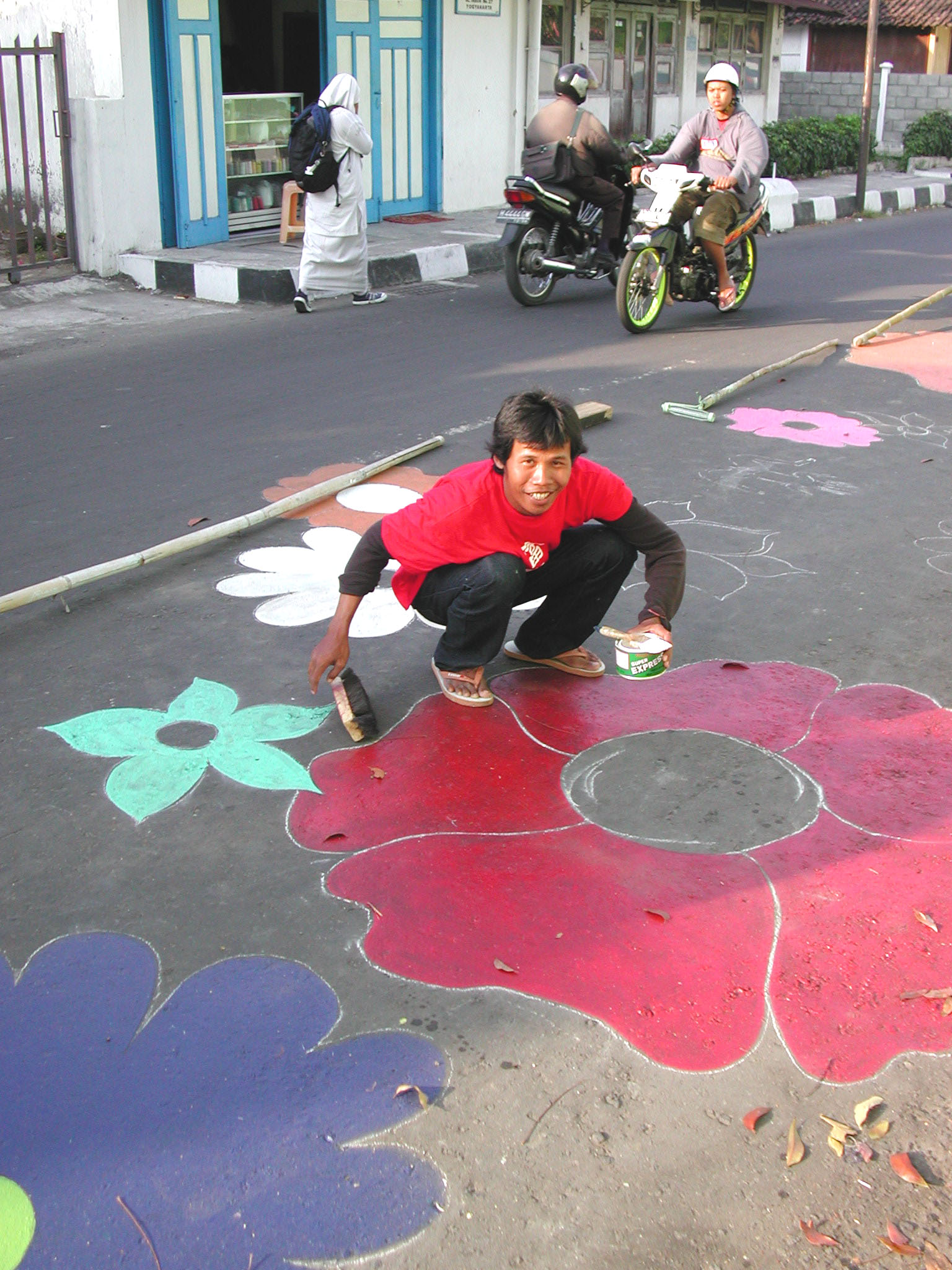 Megan Farhan painting flowers on road.jpg