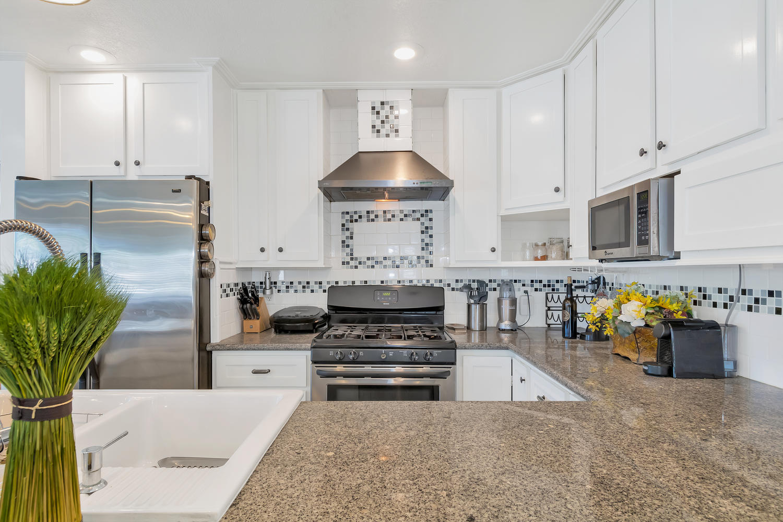 Beautiful kitchen with farm style basin sink, granite counters & adorable tile backsplash.