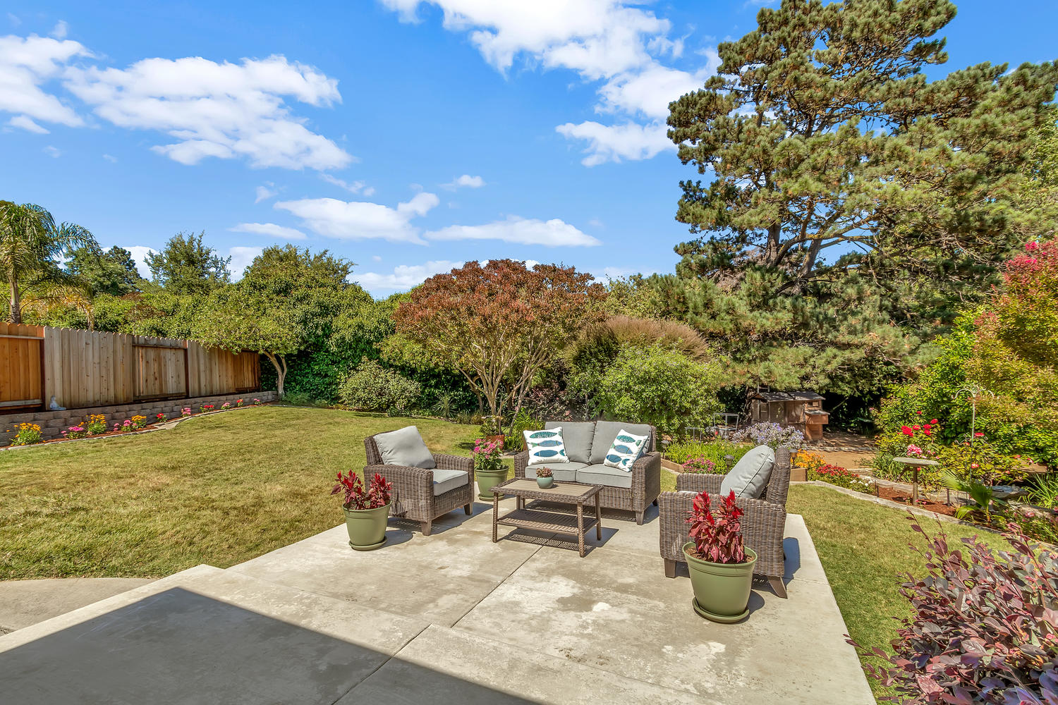 The secluded backyard offers a park-like setting with mature trees and professional landscaping.