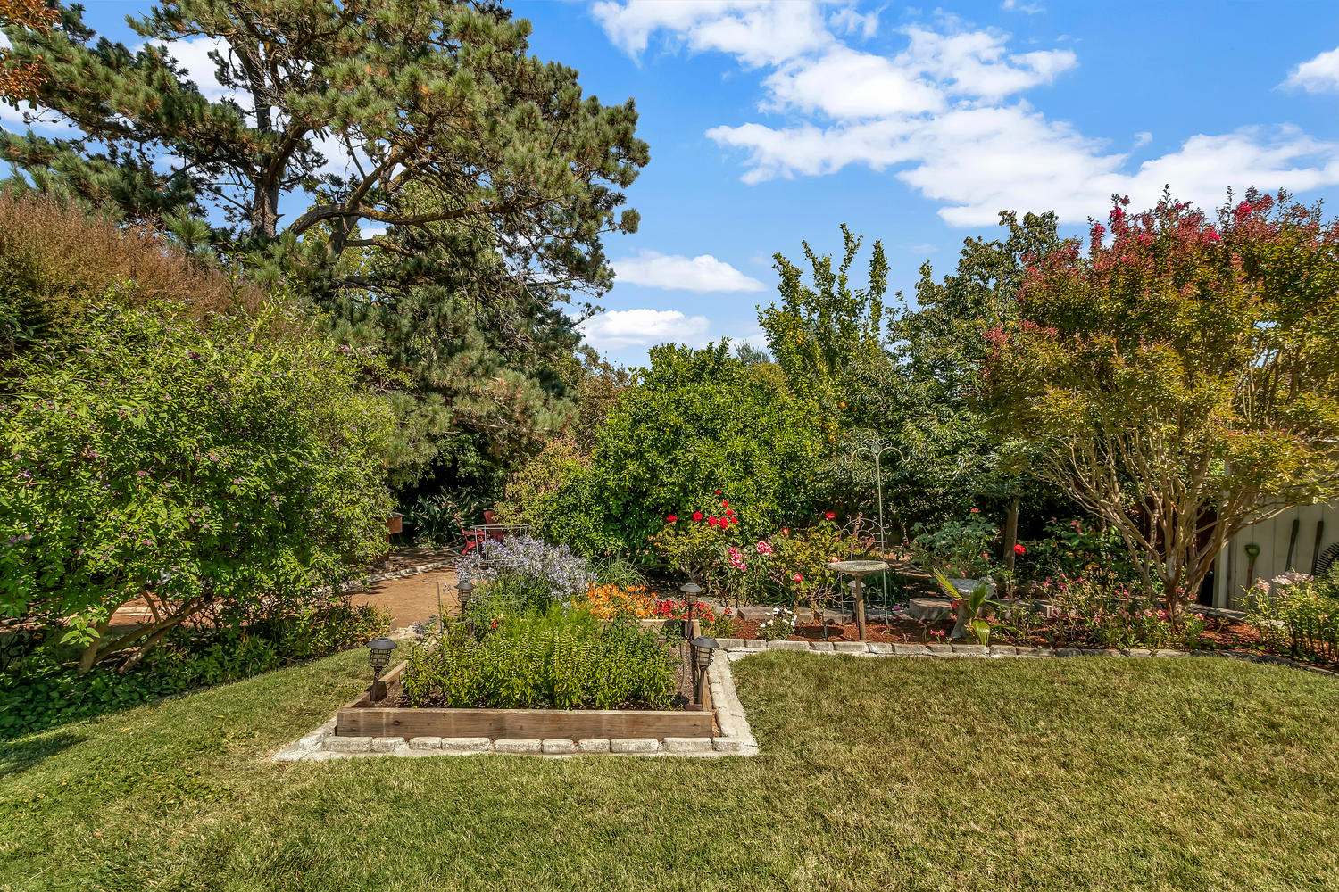The secluded backyard offers a park-like setting with mature trees, roses and professional landscaping.