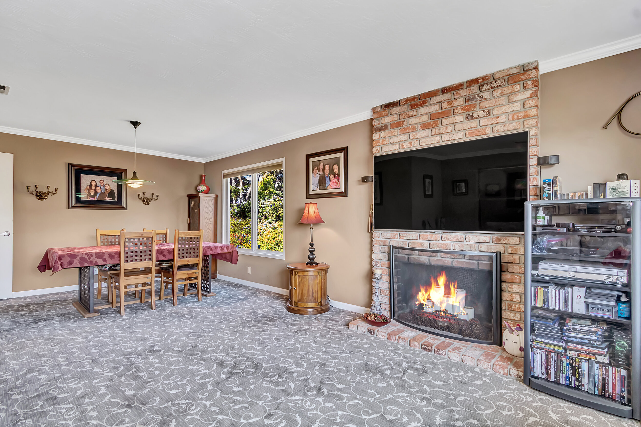 Spacious combined living/dining area with floor-to-ceiling brick fireplace.