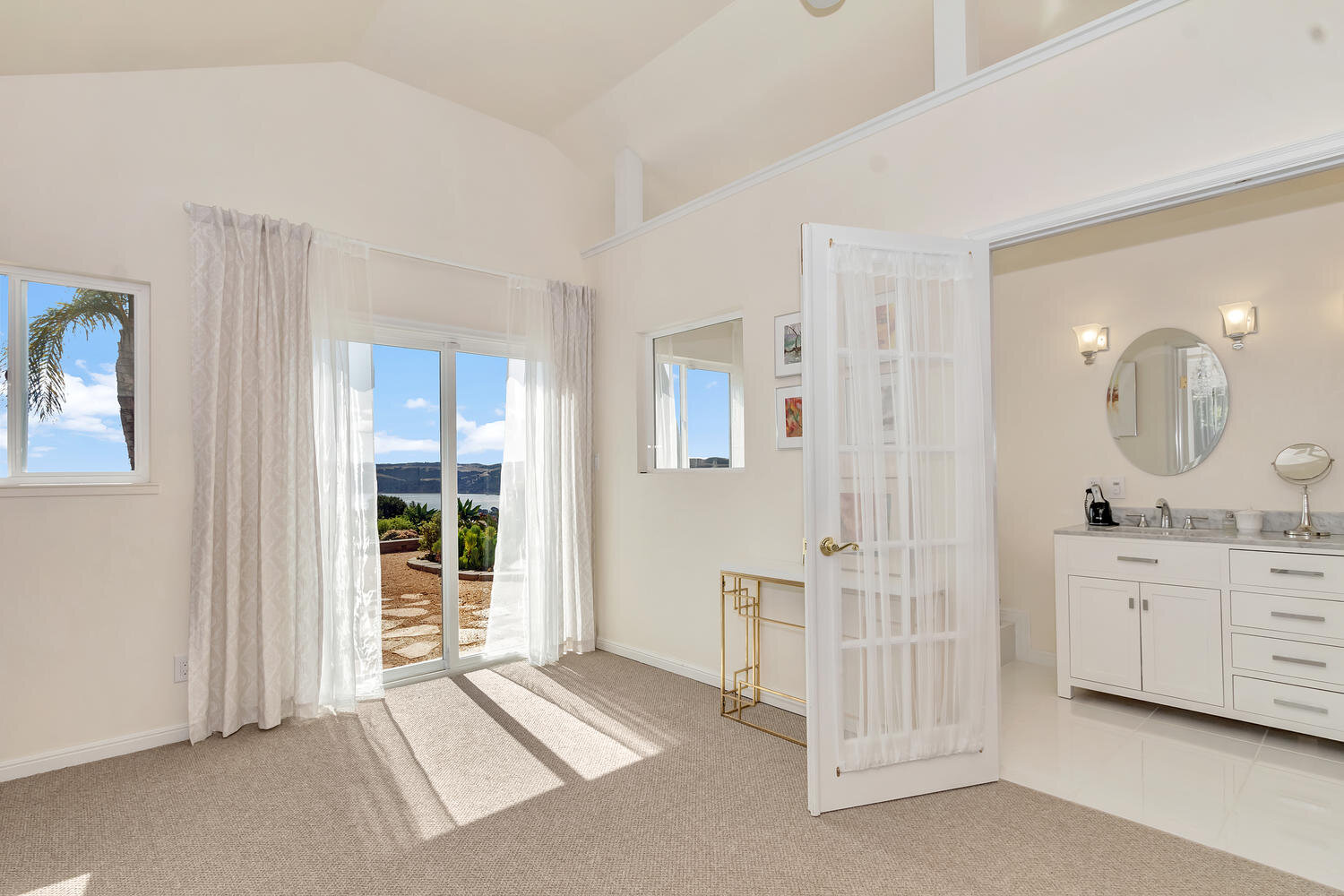 Master suite leading to patio with water view.