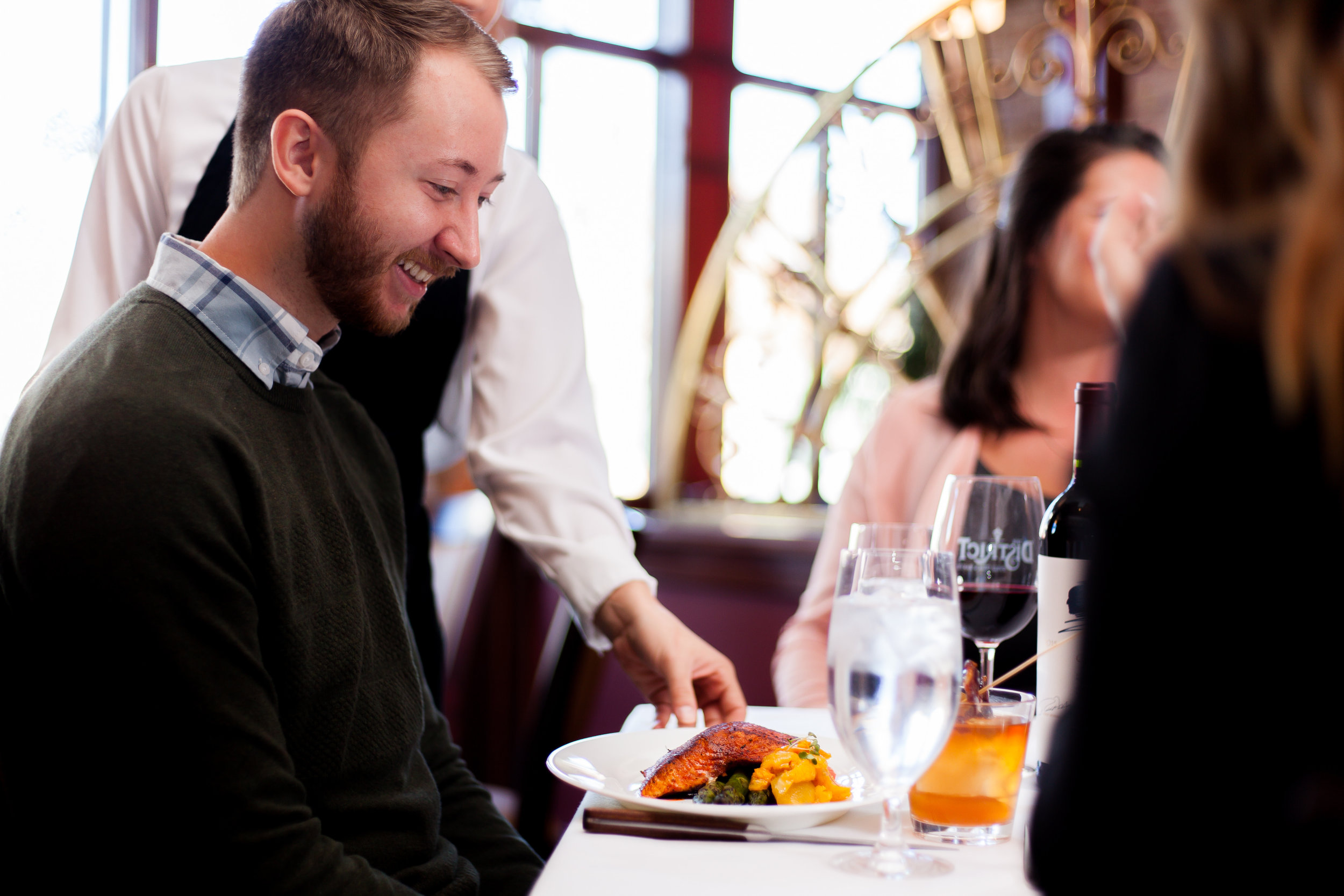 Male customer being served a fish dish by a female server.