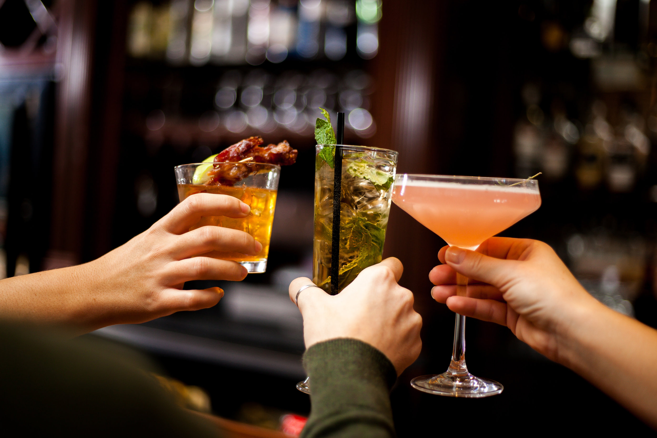 Picture of three cocktails being held and cheering at the bar.