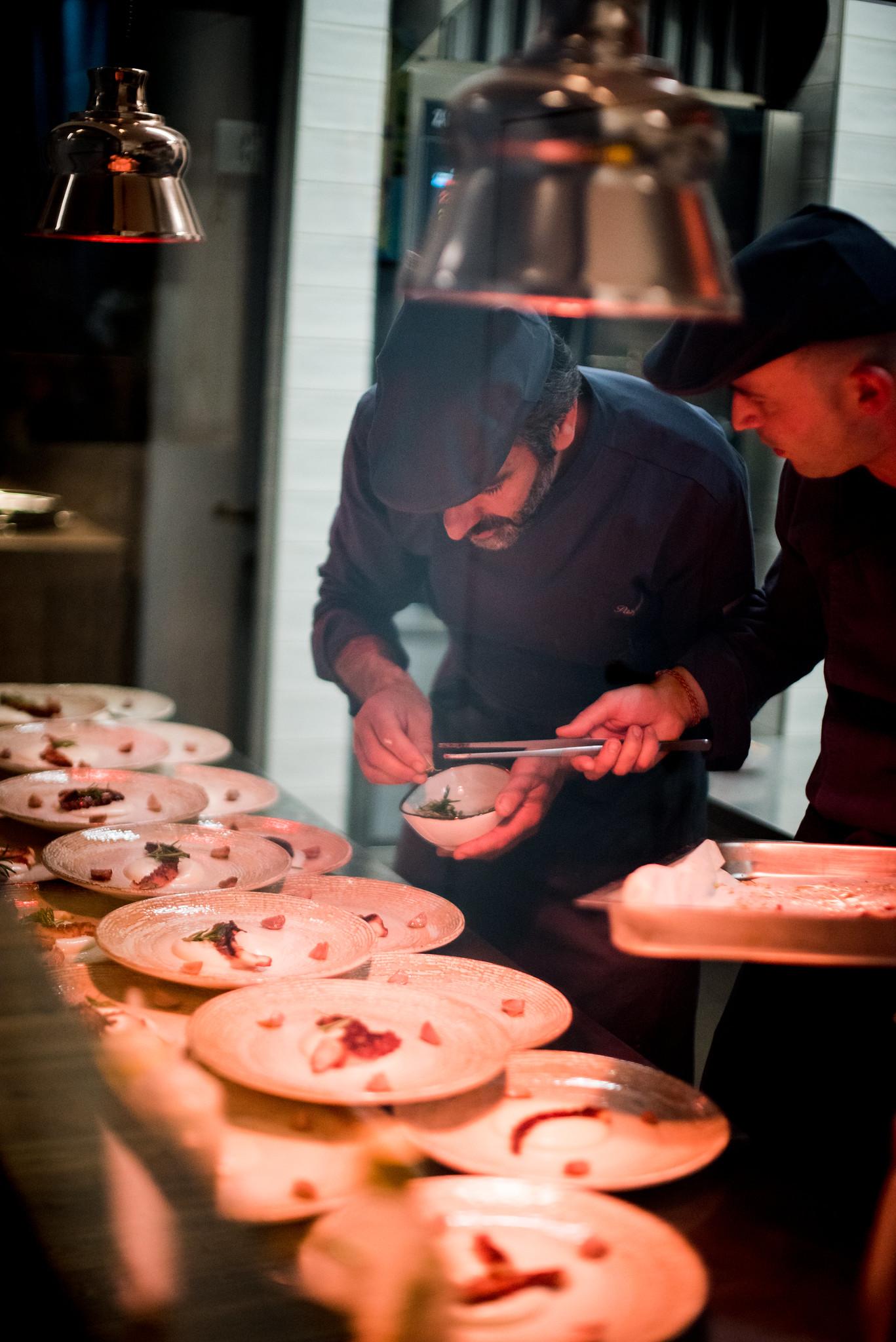 Chefs prepare the octopus course.