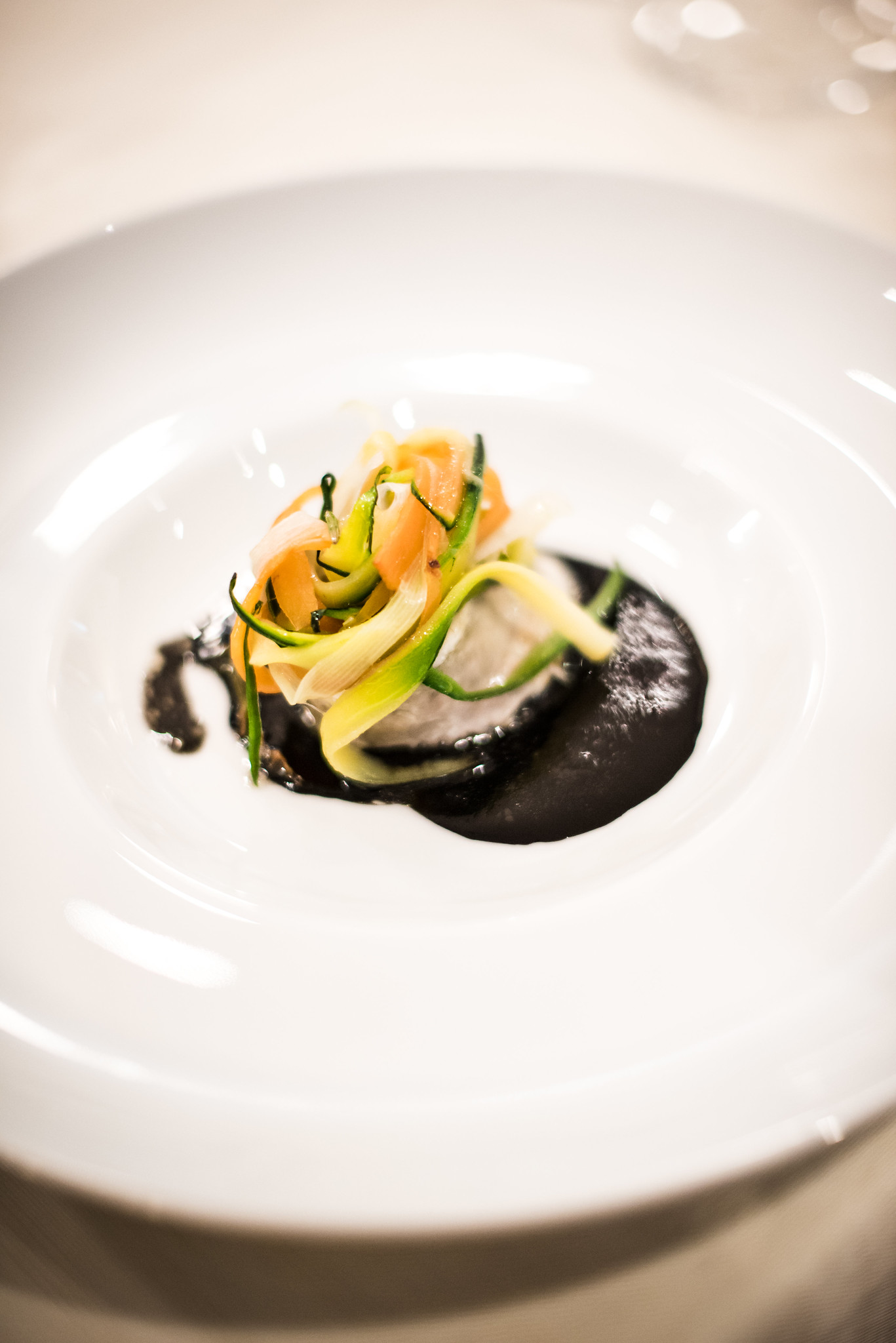A delicate branzino is served with a vegetable medley and black squid ink sauce.
