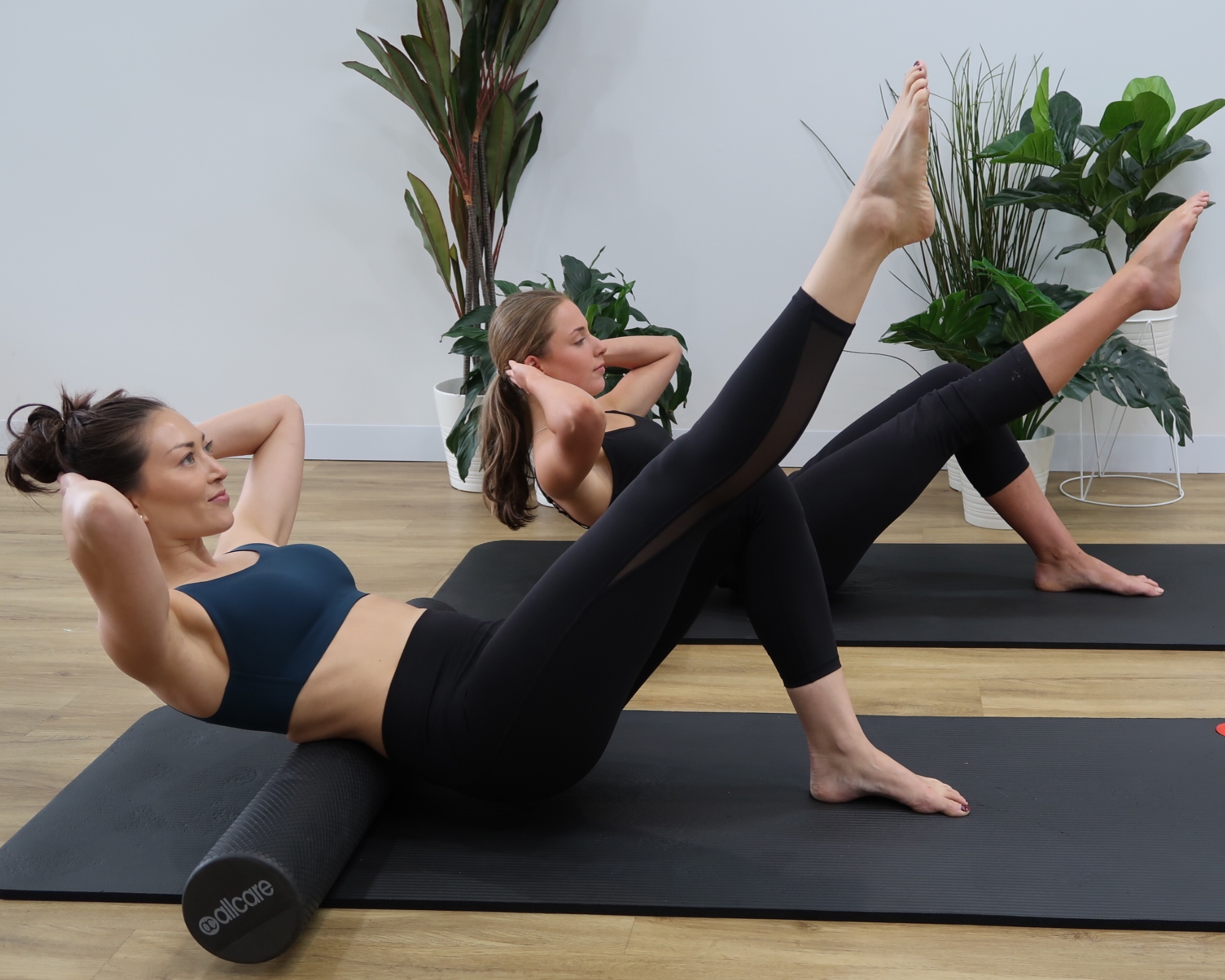 Two people doing leg exercises in Keilor Road Physio's pilates studio