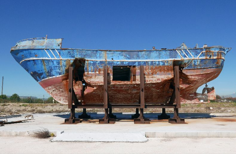Seen here at the Italian Navy base in Melilli, Sicily, the fishing boat that normally would have accommodated a crew of fifteen but was carrying hundreds of migrants when it was shipwrecked in the Mediterranean on 18 April 2015. Photo © Christoph Büchel/BARCA NOSTRA