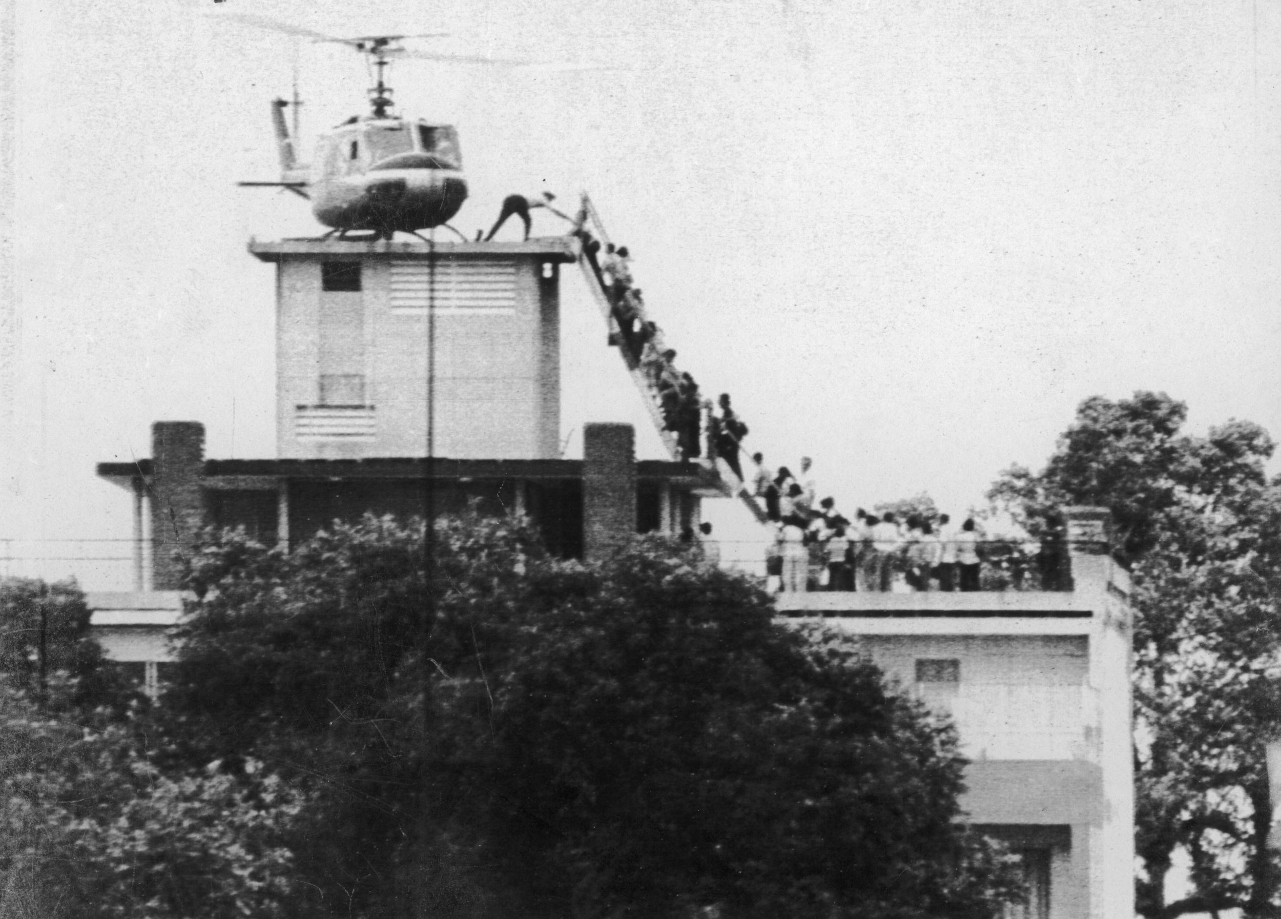 Hugh Van Es, 29th April, 1974; An Air America helicopter crew member helps evacuate people from the roof of the American Embassy, Saigon. Part of operation 'Frequent Wind', the helicopter evacuation of over 1,000 Americans and 5,000 Vietnamese from the city.