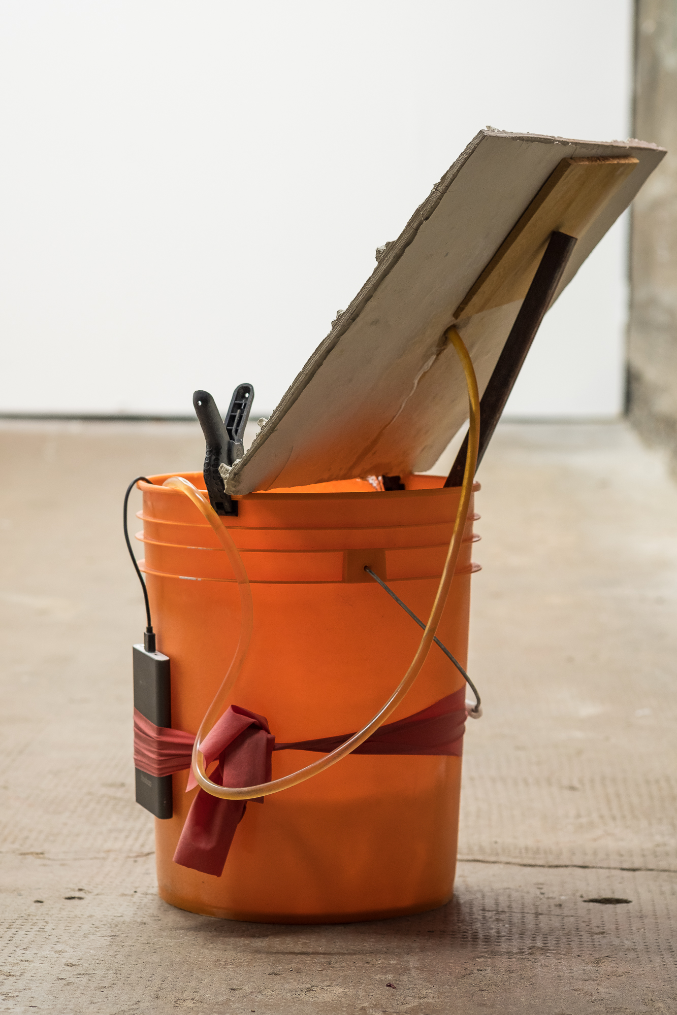 Shanie Tomassini, Leaking Hurricane, 2018. Cement, metal, water, rust, bucket, clamps, plastic tubing, USB pump, power bank, resistance band [Photo by Morgane Clément-Gagnon]
