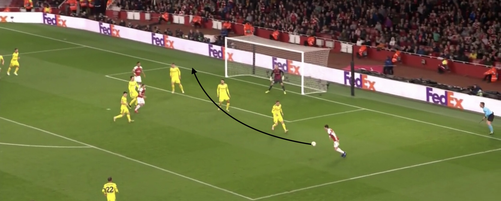 In this photo, Ozil has made a run to the back post and received a cross from the opposite side of the field. He adjust his body to face the goal and chest with his first touch then clips a cross to the back post with his second touch, again playing a forward penetrating pass.