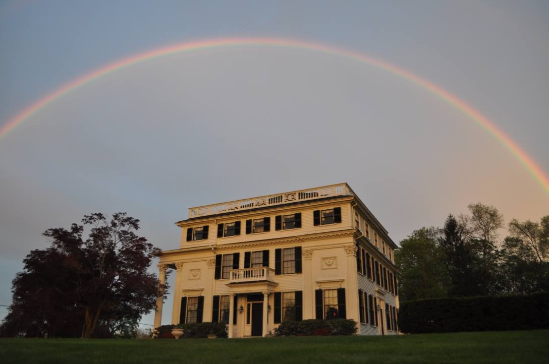 The Asa Waters Mansion as viewed from Elm Street with a resplendent rainbow, summer. Photo: Amy George.