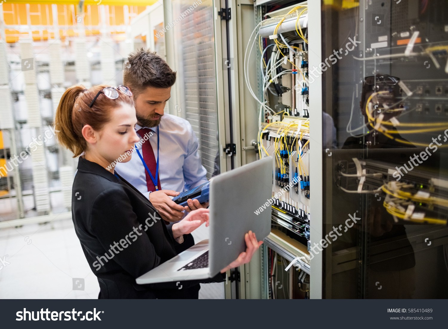 stock-photo-technicians-using-laptop-while-analyzing-server-in-server-room-585410489.jpg