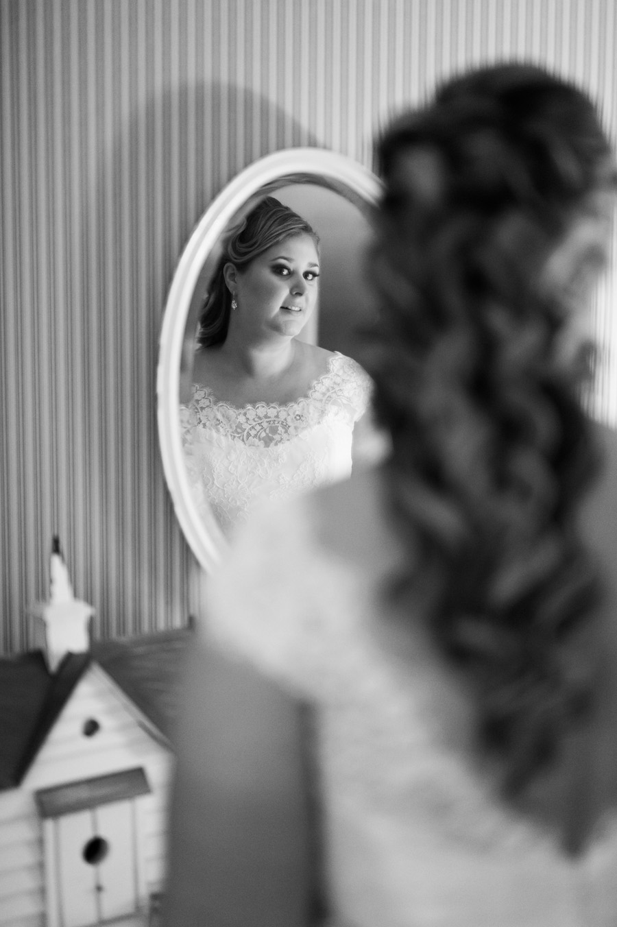 Photo of bride looking into mirror.