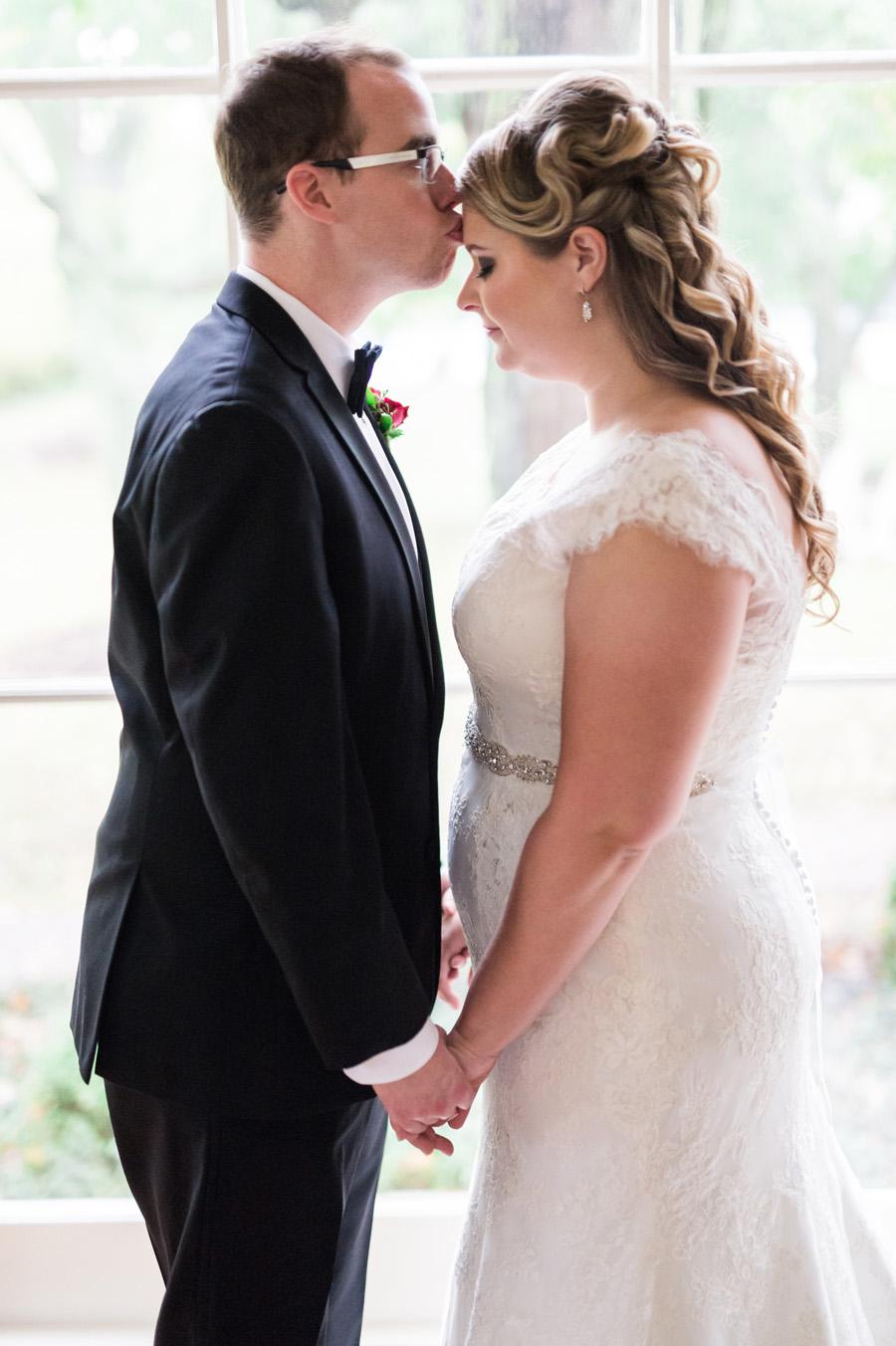 Groom kisses bride on her forehead.