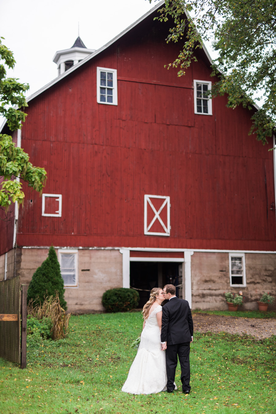 Bride and groom kiss in front of red barn.