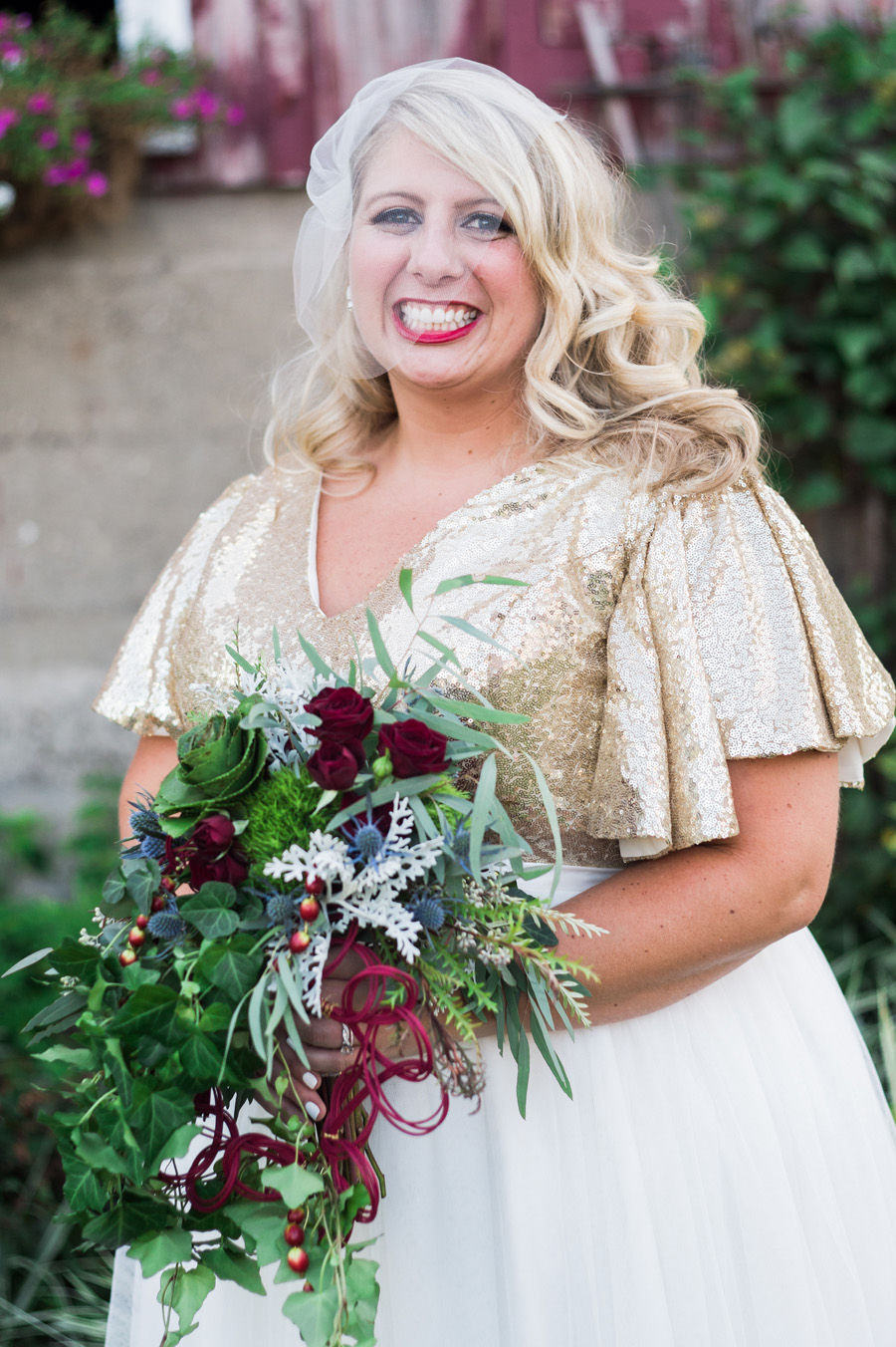 Portrait of bride in front of barn.