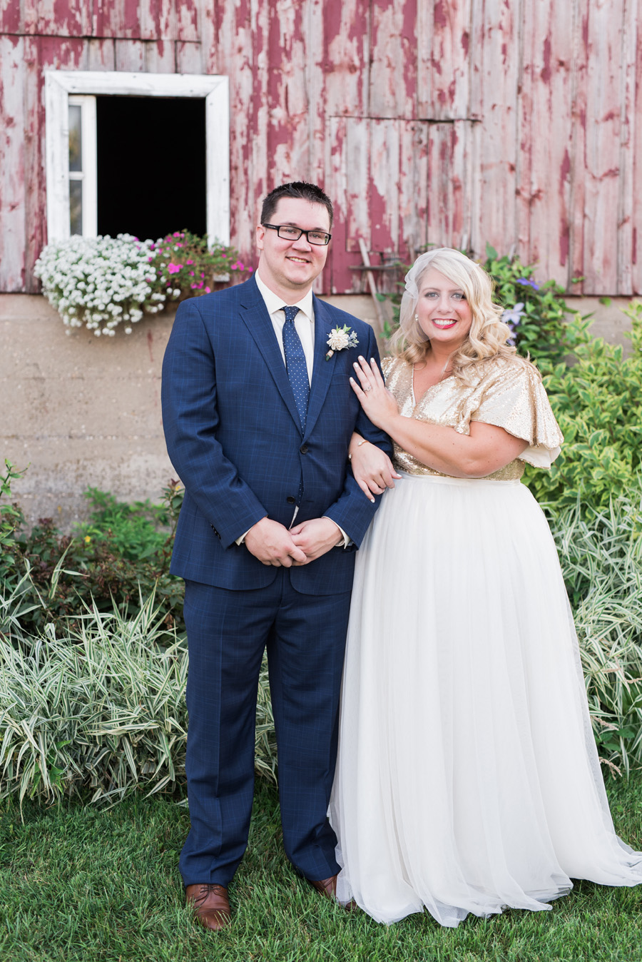 Bride and groom portrait in front of barn.