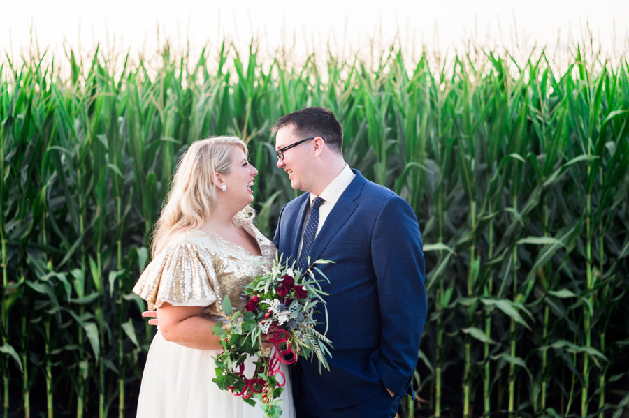 Portrait of bride and groom in front of a cornfield.