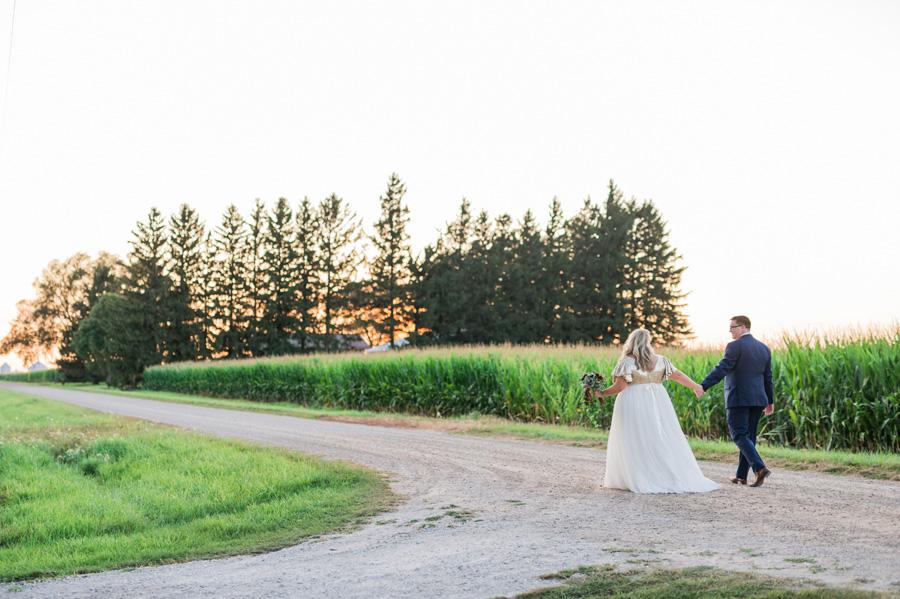 Bride and groom walking down rural road at Mora Farm.