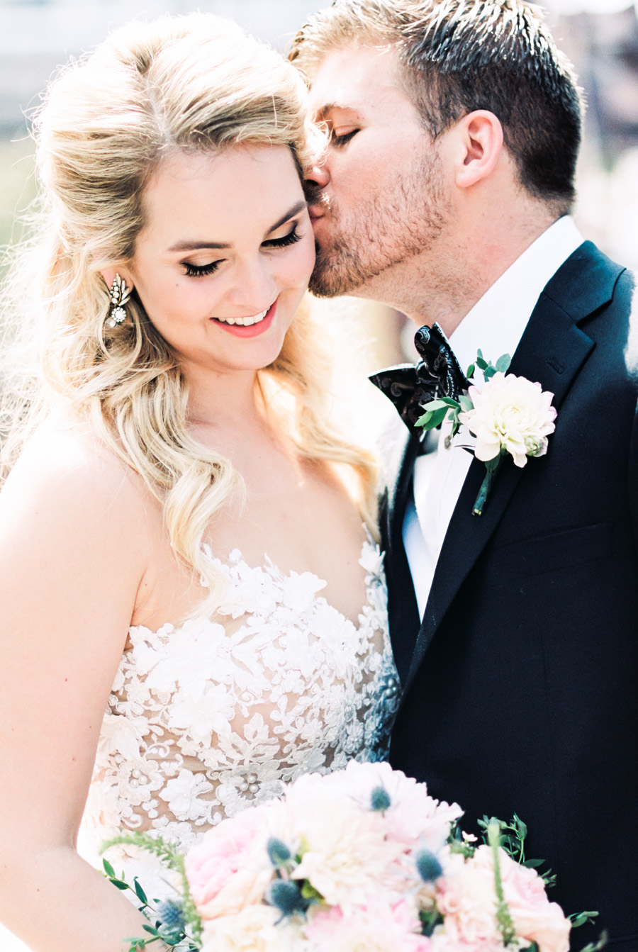 Groom kisses his bride on the cheek.