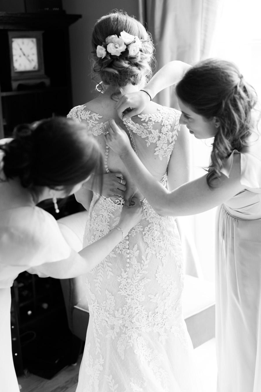 Bridesmaids helping bride get in her dress.