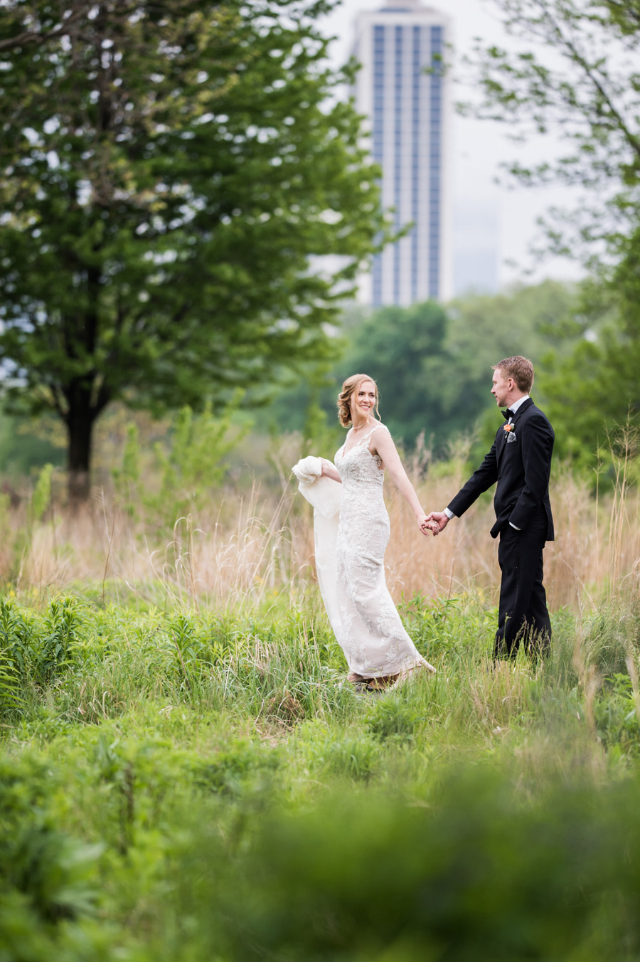 Bride and groom walk along path at Lincoln Park in Chicago.