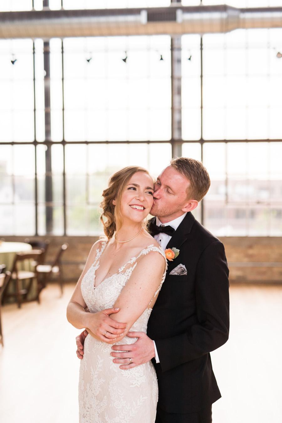 Groom kisses bride at Ravenswood event center.