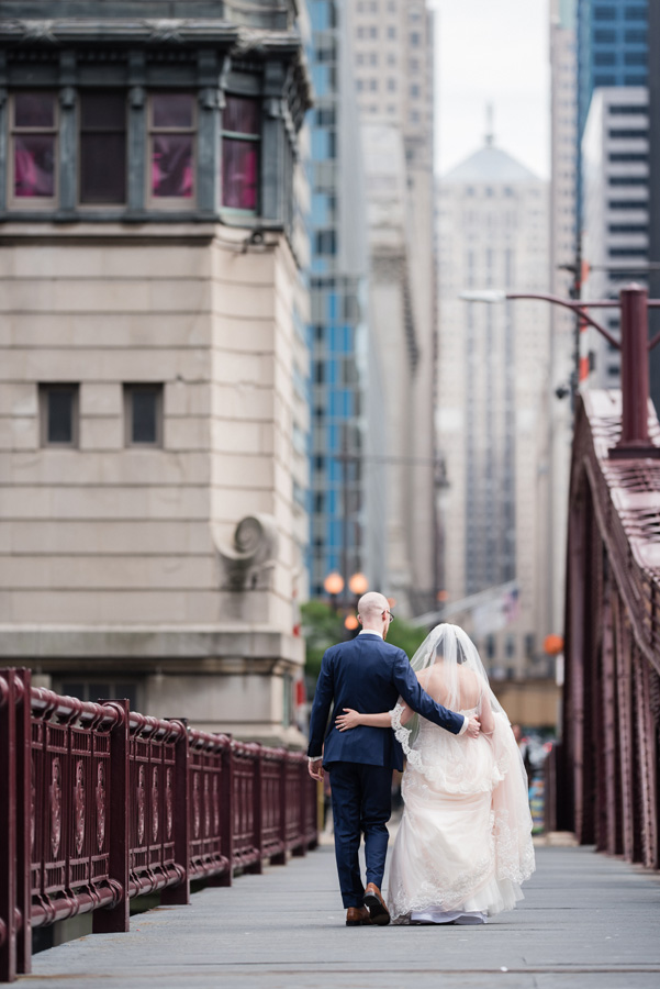 Bride and groom walk together along LaSalle Avenue bridge.