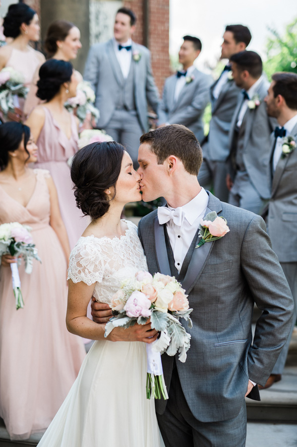 Bride and groom kiss with bridal party in background.