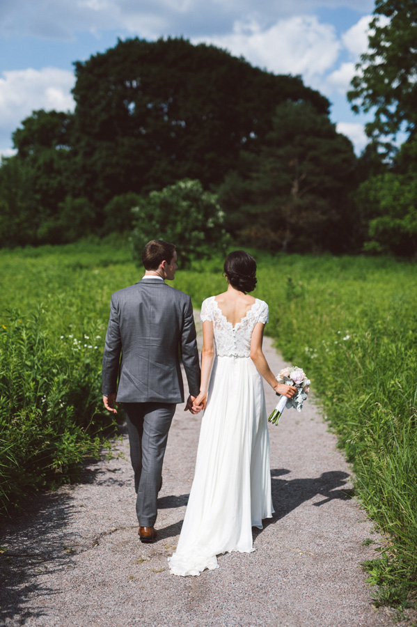 Bride and groom walk in field at Cantigny Park.