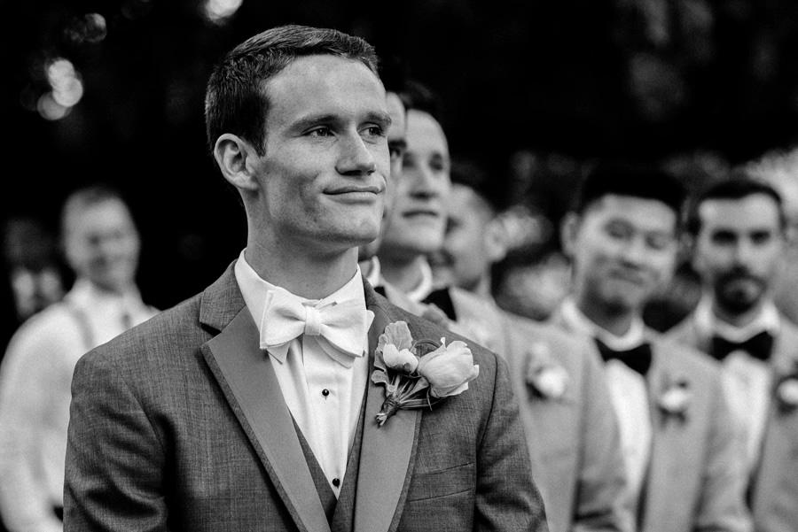 Groom watches as bride walks down the aisle.