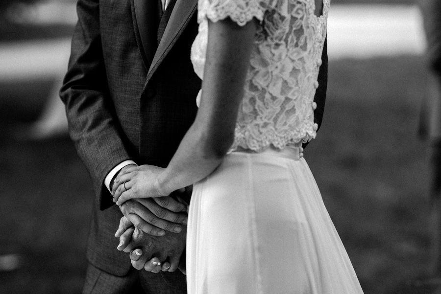 Bride and groom hold hands at wedding ceremony.