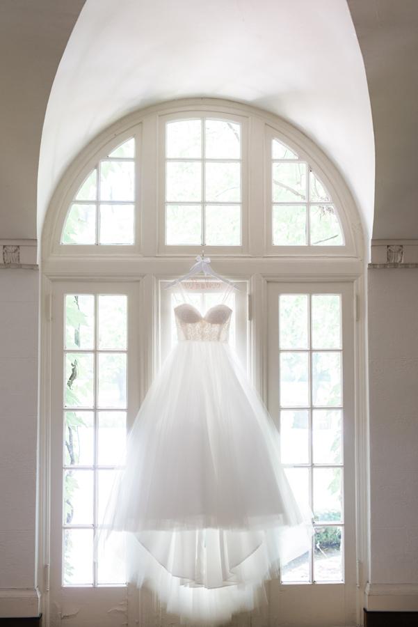 Wedding dress hanging up in window.