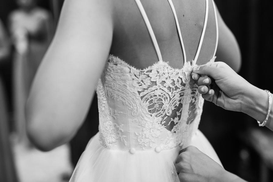 Bride's dress gets zipped up.