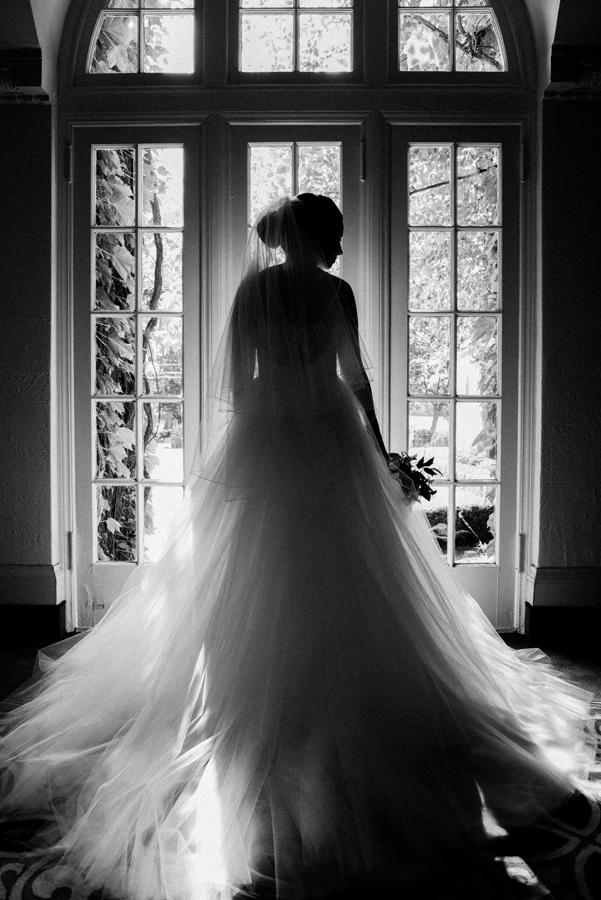 Backlit portrait of bride in window.