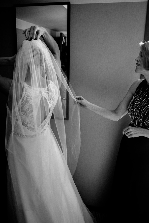 Mom helps bride put on her veil.
