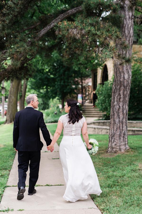 Bride and groom walk towards their church.
