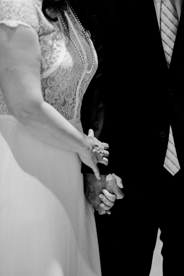 Bride and groom hold hands at weddig ceremony.