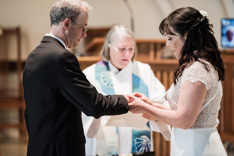 Bride and groom exchange rings at wedding ceremony.