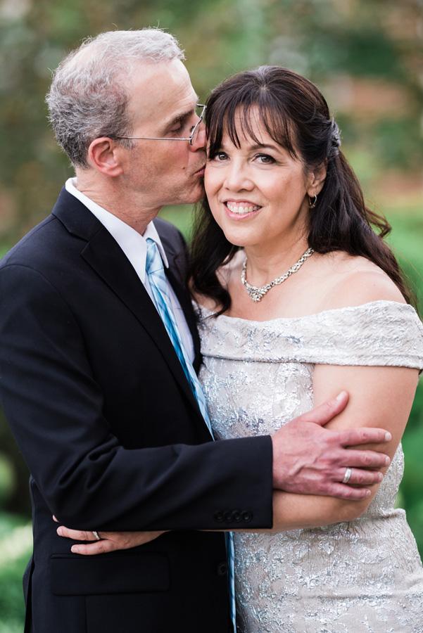 Groom kisses his bride on cheek.