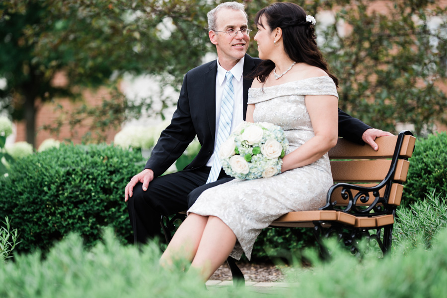 Portrait of bride and groom sitting on bench in Hinsdale.