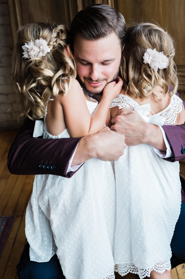 Groom gets a hug from his flower girls.