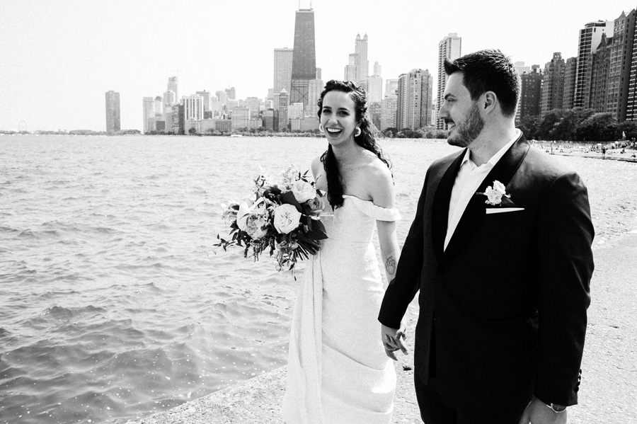 Bride and groom walk along path at North Ave Beach, Chicago.
