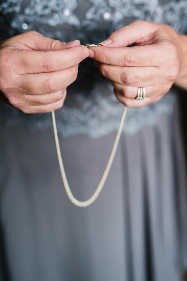 Mom holding grandma's necklace.