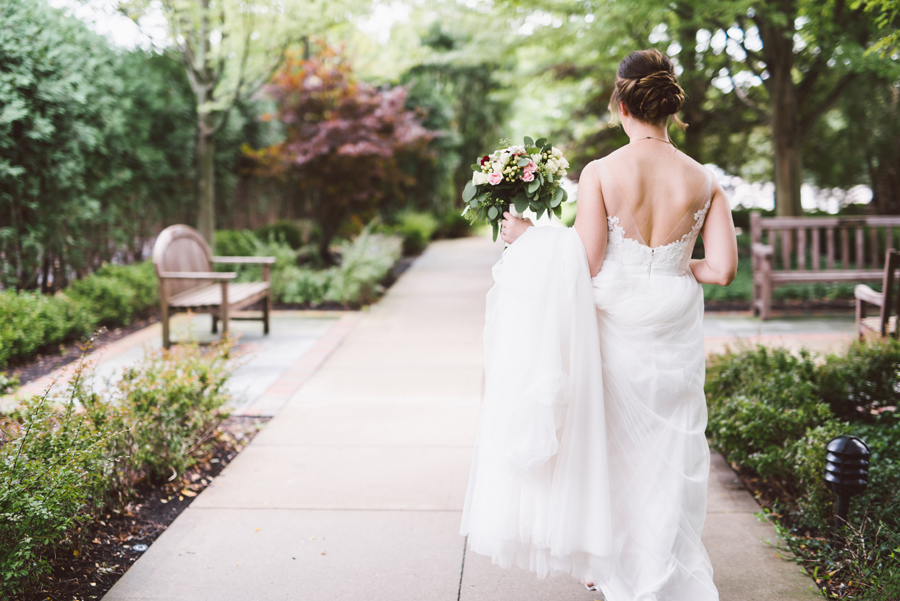 Bride walking in garden.